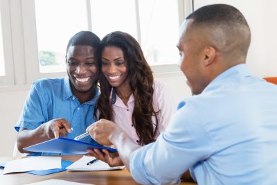 agent presenting contract to african american couple